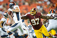 Landover, MD - August 24, 2018: Denver Broncos quarterback Paxton Lynch (12) avoids a sack by Washington Redskins defensive tackle Tim Settle (97) during preseason game between the Denver Broncos and Washington Redskins at FedEx Field in Landover, MD. The Broncos defeat the Redskins 29-17. (Photo by Phillip Peters/Media Images International)