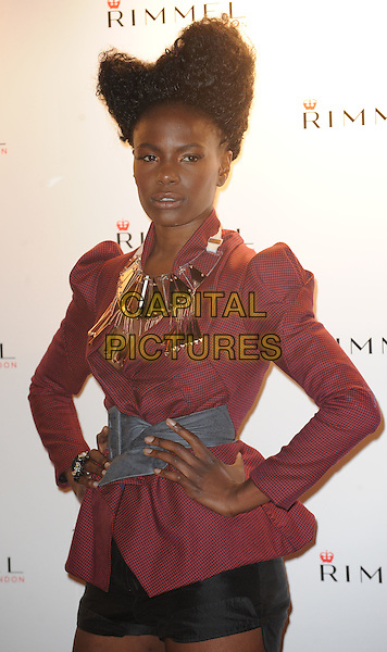 Shingai Shoniwa of The Noisettes.The Rimmel London party, Battersea Power Station, London, England..September 15th, 2011.half length black shorts brown burgundy maroon jacket gold necklace grey gray belt hair up hands on hips.CAP/WIZ.© Wizard/Capital Pictures.