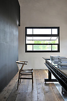 A functional, black and white space with a wood floor. The room is furnished with a long black iron table with a polished top and a light wood chair.