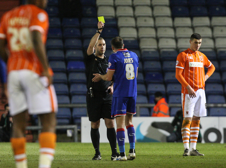 Referee Jeremy Simpson shows Oldham Athletic's Mike Jones a yellow card after a fracas with Blackpool's Luke Higham<br /> <br /> Photographer Alex Dodd/CameraSport<br /> <br /> Football - The Football League Sky Bet League One - Oldham Athletic v Blackpool - Tuesday 15th March 2016 - SportsDirect.com Park - Oldham   <br /> <br /> &copy; CameraSport - 43 Linden Ave. Countesthorpe. Leicester. England. LE8 5PG - Tel: +44 (0) 116 277 4147 - admin@camerasport.com - www.camerasport.com