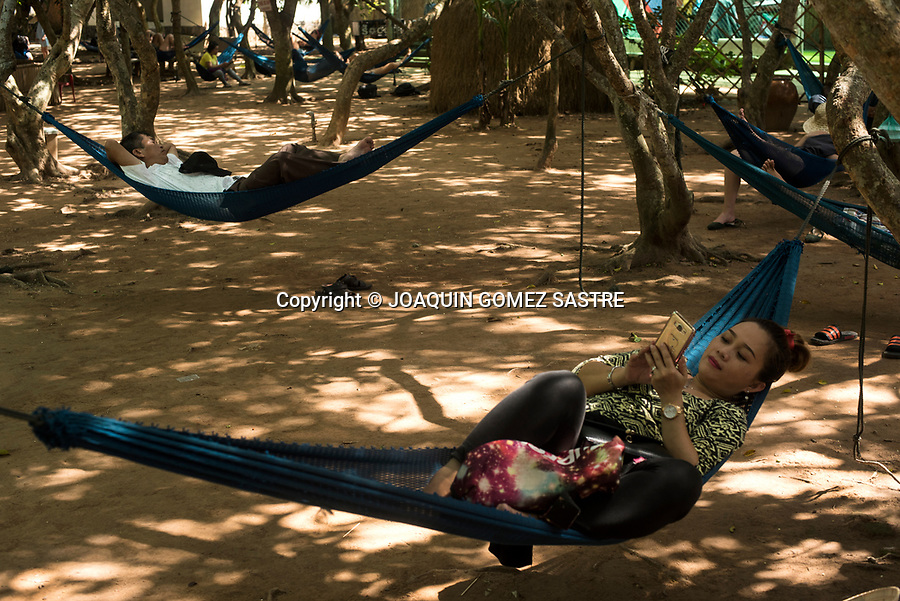 A young woman checks her smartphone in a rest area with hammocks in the shade of the trees to protect herself from the heat, around the Mekong Delta (Vietnam)<br /> HO CHI MINH-VIETNAM