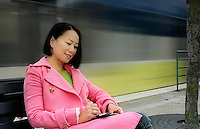 Asian woman sitting on train platform, using pda, smiling..MR