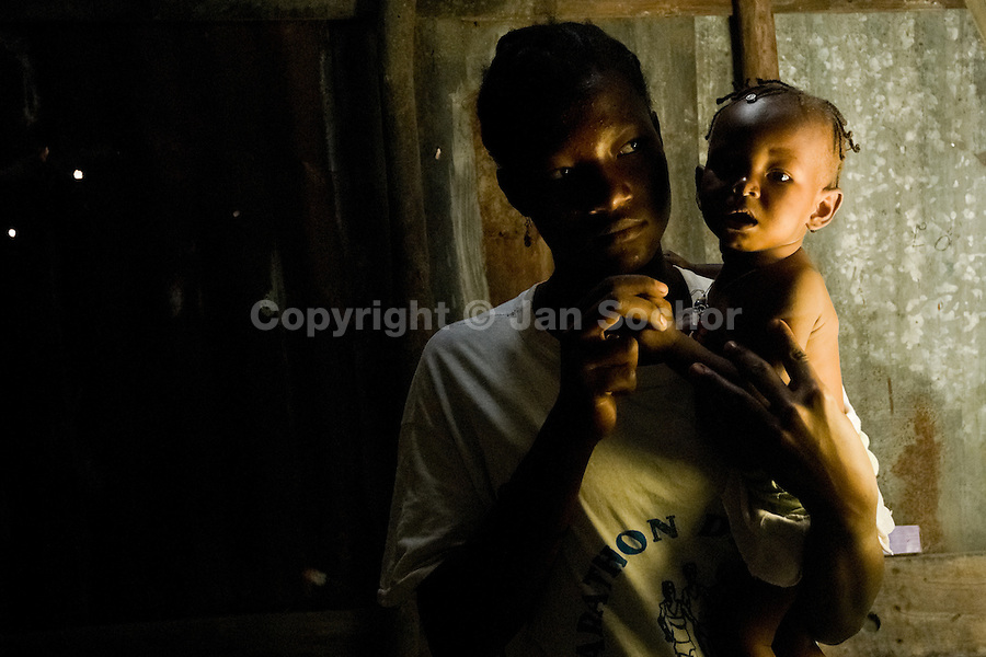 A young Haitian mother holds her baby inside the shack in the slum of Cité Soleil, Port-au-Prince, Haiti, 11 July 2008. Cité Soleil is considered one of the worst slums in the Americas, most of its 300.000 residents live in extreme poverty. Children and single mothers predominate in the population. Social and living conditions in the slum are a human tragedy. There is no running water, no sewers and no electricity. Public services virtually do not exist - there are no stores, no hospitals or schools, no urban infrastructure. In spite of this fact, a rent must be payed even in all shacks made from rusty metal sheets. Infectious diseases are widely spread as garbage disposal does not exist in Cité Soleil. Violence is common, armed gangs operate throughout the slum.