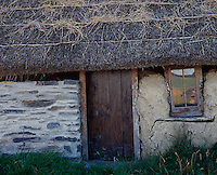 The adjacent barn has a thatched roof and a window at a rakish angle