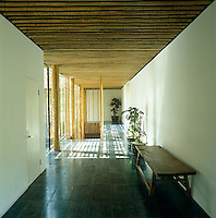 A tranquil corridor with a bamboo ceiling is furnished with a rustic wooden bench