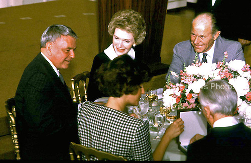 Washington, DC - May 23, 1985 - Frank Sinatra, first lady Nancy Reagan, and Chuck Yeager have lunch after the Medal of Freedom ceremony at The White House in Washington, DC on May 23, 1985.<br /> Credit: Arnie Sachs / CNP
