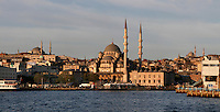 General view of The New Mosque or Mosque of the Valide Sultan (Yeni Cami, Yeni Valide Camii), 1597-1663, by Davut Aga, Dalgic Ahmed Cavus, and Mustafa Aga, Istanbul, Turkey, at dawn, from the sea. This Ottoman Imperial mosque stands on the Golden Horn at the southern end of the Galata Bridge. Originally commissioned by Safiye Sultan the project was finished after many delays by another valide Sultan, Turhan Hadice. The historical areas of the city were declared a UNESCO World Heritage Site in 1985. Picture by Manuel Cohen.