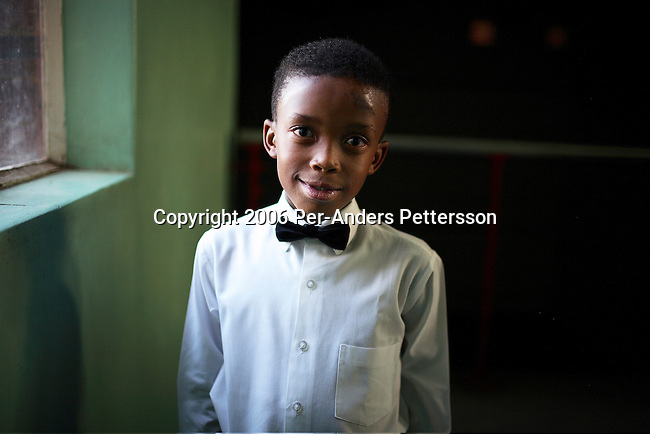 SOWETO, SOUTH AFRICA OCTOBER 25: A young ballroom dancer poses before he starts rehearsing in a community hall in Pimville Community center on October 25, 2006 in Soweto, Johannesburg, South Africa. Ballroom dancing is very popular sport in the township and all over the country. Soweto is South Africa?s largest township and it was founded about one hundred years to make housing available for black people south west of downtown Johannesburg. The estimated population is between 2-3 million. Many key events during the Apartheid struggle unfolded here, and the most known is the student uprisings in June 1976, where thousands of students took to the streets to protest after being forced to study the Afrikaans language at school. Soweto today is a mix of old housing and newly constructed townhouses. A new hungry black middle-class is growing steadily. Many residents work in Johannesburg, but the last years many shopping malls have been built, and people are starting to spend their money in Soweto.  .(Photo by Per-Anders Pettersson/Getty Images)..