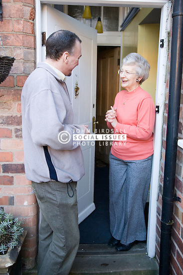 Older woman greeting an IndependentAge volunteer at her front door,