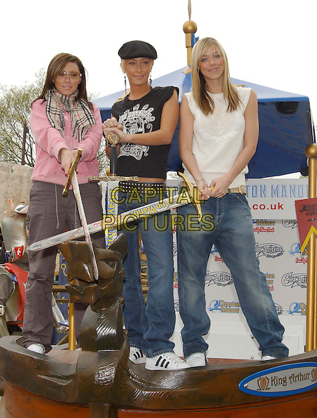 "ATOMIC KITTEN - NATASHA HAMILTON,  JENNY FROST, LIZ McCLARNON.launch new family adventure ride ""Excalibur-A Dragon's Tale"" at Drayton Manor Theme Park.April 24th, 2003.full length jeans denim white black pink burberry scarf hat sword.CAP/PL.©Capital Pictures"