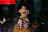 A woman sells squid from her small stall in the city of Wuhan, central China.<br />