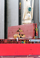 Workers aboard the Federal Champlain of Majuro, load the grain carrier at the Cargill AfHorizons terminal, Sarnia Bay. A worker in white coveralls guides a grain loaded scoop while balancing the load.