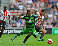 Kyle Naughton of Swansea City is pushed off the ball by Jack Rodwell of Sunderland during the Barclays Premier League match between Sunderland and Swansea City played at Stadium of Light, Sunderland