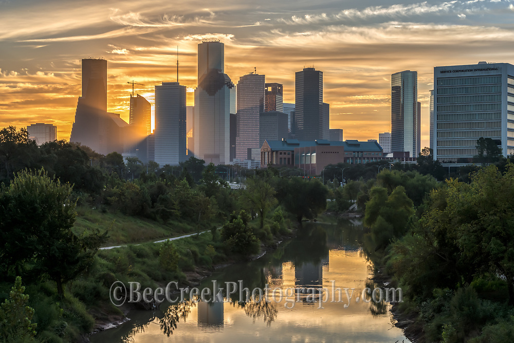We were almost ready to leave and then sky turned into this golden swirling clouds over the skyline of the Bayou and city skyline so we had to take a few more images.  You can see the sun just starting to peak through the high rise skyscrapers and the buildings reflections in the water of the Buffalo Bayou on this early morning sunrise. Watermark will not appear on image