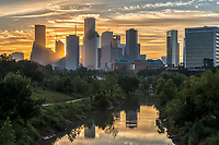 Houston Skyline Golden Glow -  We were almost ready to leave and then sky turned into this golden swirling clouds over the skyline of the Bayou and city skyline so we had to take a few more images.  You can see the sun just starting to peak through the high rise skyscrapers and the buildings reflections in the water of the Buffalo Bayou on this early morning sunrise. Watermark will not appear on image
