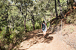 Woman walking through woodland trees Sierra Morena mountains, Sierra de Aracena, Huelva province, Spain