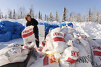 "February 16, 2013  Volunteer Jennifer Ambrose piles musher food bags bound for Skwentna and which will be loaded into volunteer Iditarod Air Force planes at the Willow Airport during day one of the ""Food Fly""...Photo Copyright Jeff Schultz  -- Do not reproduce without written permission"