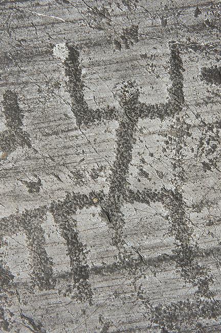 "Petroglyph, rock carving, of a schematic human figures in the so called ""Prayer"" position. Carved by the ancient Camuni people in the Late Copper Age between 3200- 2200 BC. Rock no 24,  Foppi di Nadro, Riserva Naturale Incisioni Rupestri di Ceto, Cimbergo e Paspardo, Capo di Ponti, Valcamonica (Val Camonica), Lombardy plain, Italy"