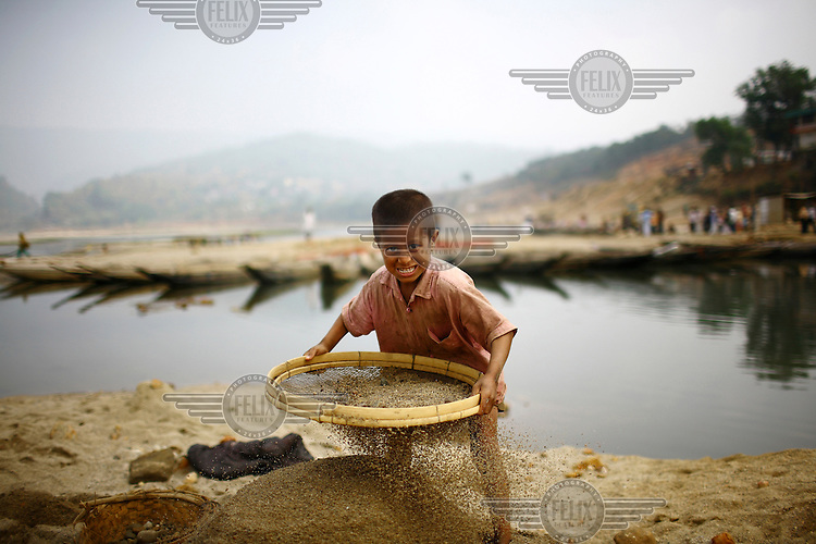 A boy sieves sand on the banks of the Piyain River. At least 10,000 people, including 2,500 women and more than 1,000 children, are engaged in stone and sand collection from the Bhollar Ghat. Building materials such as stone and sand, and the cement which is made from it, are in short supply in Bangladesh and therefore command a high price from building contractors. The average income for these workers is around 150 taka (less than GBP 1.33) a day.