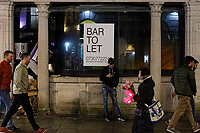 Pictured:A man rests against a bar property in Wind Street, Swansea, Wales, UK. Friday 20 December 2019<br /> Re: Black Eye Friday (also known as Black Friday, Mad Friday, Frantic Friday) the last Friday before Christmas, in Swansea, Wales, UK.