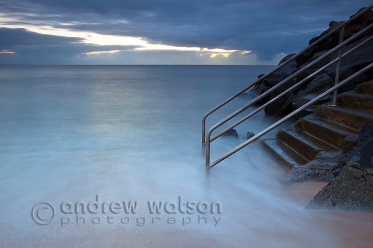 Waves washing over steps at Machans Beach, Cairns, Queensland, Australia
