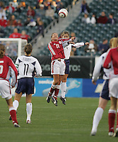 06 November,  2004. UWNT defender Cat Reddick (4) goes up for a header against Merete Pedersen (11) of Denmark  at  Lincoln Financial Field in Philadelphia, Pa.