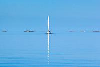 Segelbåt i spegling på lugnt hav utanför Huvudskär i Stockholms södra ytterskärgård.