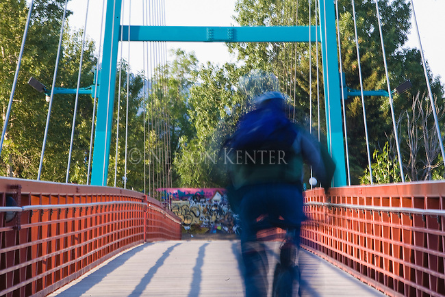 A bike rider uses a footbridge over the Clark Fork River in Missoula, Montana