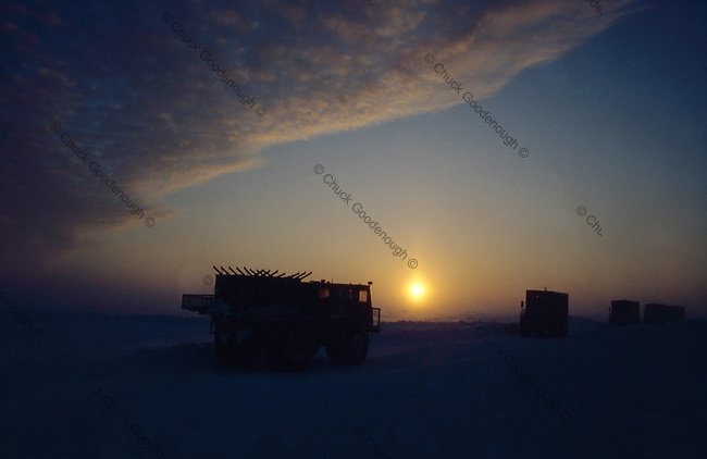 "Stock Photo circa 1980 of Winter Alaska Oil exploration vehicles at sunset. The foreground vehicle held the ""Juggies"" and their ""jugg's"" or Geophones which they would lay down on the ice. The Vibrators would then send seismic waves into the earth which would refelct back into the juggs and be recorded to show the density of rock in the earths crust."