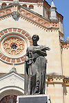 A statue on a World War II memorial of a woman holding a sword and a palm leaf in front of a church in Tremezzo, a town on Lake Como, Italy.