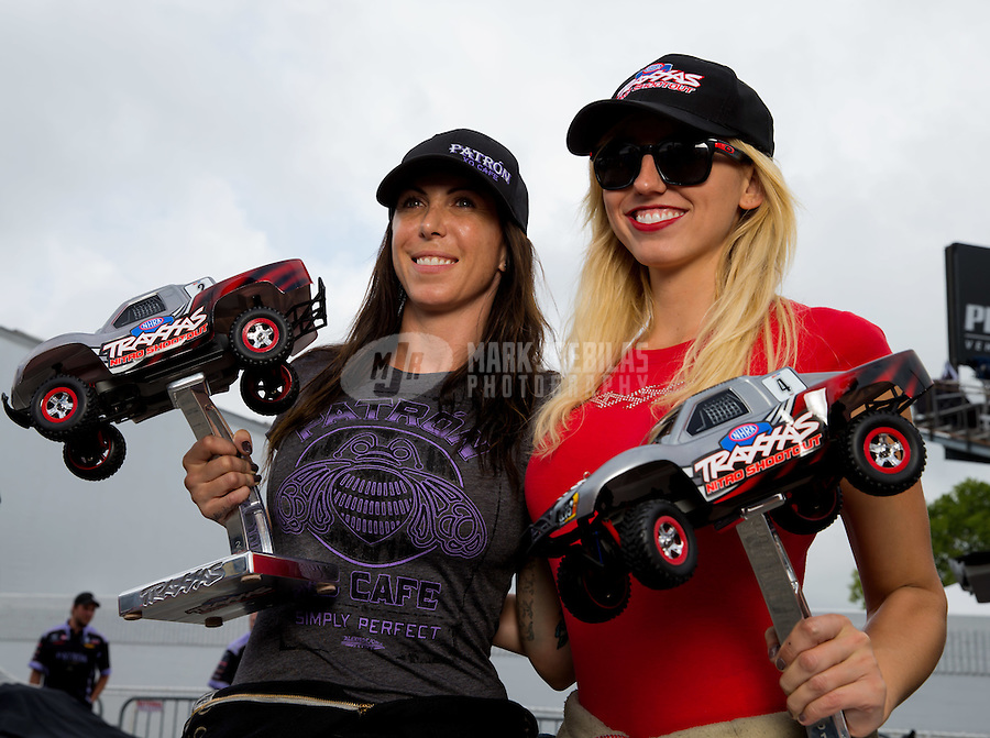 Aug 31, 2014; Clermont, IN, USA; NHRA funny car driver Alexis DeJoria (left) poses with Courtney Force holding their Traxxas Trophies during qualifying for the US Nationals at Lucas Oil Raceway. Mandatory Credit: Mark J. Rebilas-USA TODAY Sports