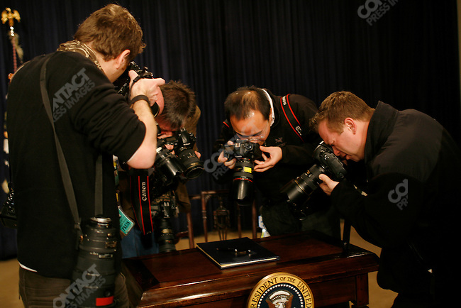 President Barack Obama signs his first executive orders allowing greater transparency in government and capping pay for senior White House staff. Executive Office Building, Washington D.C., January 21, 2009