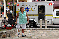 An elderly gentlemen is being looked at by paramedics, while this lady on crutches manages a smile..