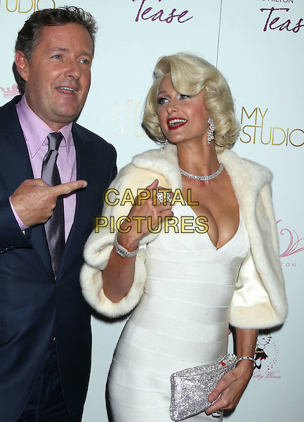 "PIERS MORGAN & PARIS HILTON.Paris Hilton and Friends celebrate the launch of Hilton's tenth fragrance ""Tease"" at MyStudio, Hollywood, California, USA..August 10th, 2010.half length white bandau dress fur cream jacket silver diamond necklace cleavage red lipstick clutch bag blue suit jacket pink shirt hand finger pointing .CAP/ADM/MJ.©Michael Jade/AdMedia/Capital Pictures."
