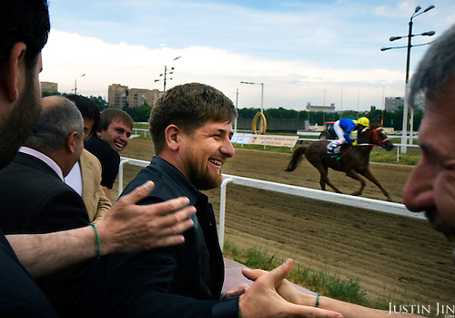"""Chechen President Ramzan Kadyrov celebrates as his horse wins a race in Moscow's Hippodrome. .Kadyrov's horse, """"Royal Quiet"""", came first in the 1600-metre race. .The horse, born in the U.S.A., is parented by father: Real Quiet, mother: Dinasoar, is trained by S. G. Kolesnikov and rode by master jockey S. V. Petin."""