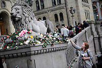 (Oslo July 25, 2011) A woman puts down flowers outside the Norwegian parliament. An estimated 150,000 people gathered in Oslo town centre for a vigil following Friday's twin extremist attacks ...A large vehicle bomb was detonated near the offices of Norwegian Prime Minister Jens Stoltenberg on 22 July 2011. .Another terrorist attack took place shortly afterwards, where a man killed 68 people, mainly children and youths attending a political camp at Utøya island. ..Anders Behring Breivik was arrested on the island and has admitted to carrying out both attacks..(photo:Fredrik Naumann/Felix Features)