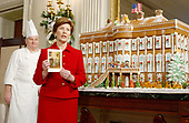 The White House Christmas decorations were shown to the press on December 3, 2001.  Even though the Executive Mansion has been closed to tourists since the 9/11 terrorist attacks, the annual ritual of decorating the house continues.  First lady Laura Bush displays this year's White House Christmas Card while standing in front of the traditional gingerbread house in the State Dining Room.  White House Pastry Chef Roland Mesnier looks on at far left.<br /> Credit: Ron Sachs / CNP