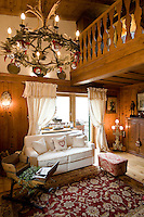 Salvaged wood from an old chalet has been used to panel the walls of this living room which also features a horn chandelier, a child's sleigh turned into a table and a 20th century Turkish rug