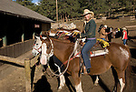 Woman outdoors at the stables preparing on a crisp and cool fall morning for riding horses in Rocky Mountain National Park, near Estes Park, Colorado, USA (MR #88)