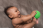 5 month old baby boy at home on back, using hands and feet to explore toy ball with bumpy surface