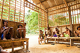 PHILIPPINES, Palawan, Barangay region, Batak men seek shelter from the sun in a building where only men are allowed, Kalakwasan Village