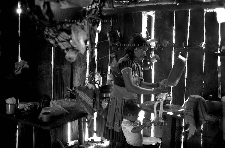 Messico, Chiapas, La Realidad.Comunità indigena Zapatista.Donna macina il mais nella sua casa.Mexico, Chiapas, La Realidad.Zapatista indigenous communities.Woman grinding corn at his home