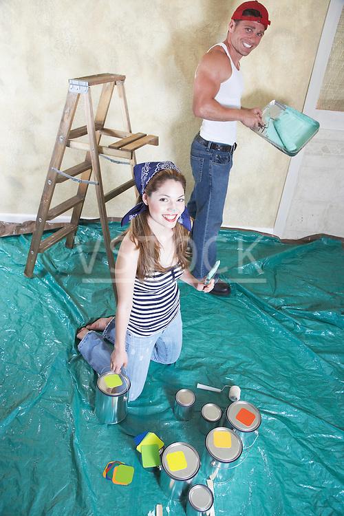 Portrait of happy couple painting room