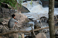 A thoughtfull fisherman in a channel of the Khone falls, Laos-2010