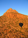 Shadow of hot air balloon on side of a mountain, shortly after dawn, Tucson, Arizona.