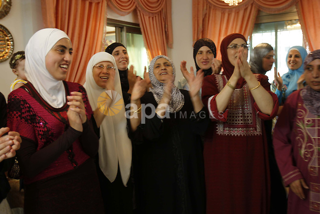 The first student of the general secondary certificate on Palestine, Tala Batyeh, 99.7, celebrate with her family in the West Bank of Nablus on July 21, 2009. Photo By Nedal Shtieh