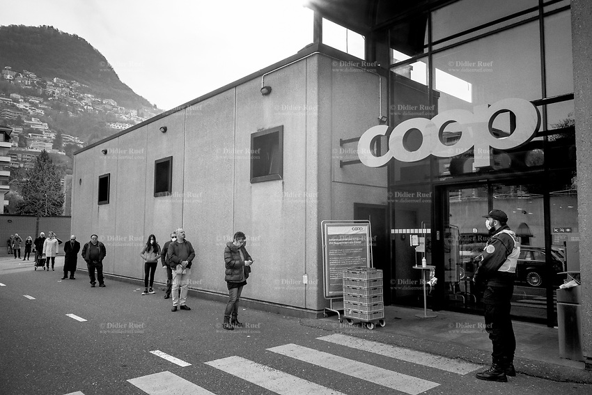 """Switzerland. Canton Ticino. Lugano. Supermarket Coop. A security guard working for the private company Securitas stands at the entrance of Coop Supermarket. The man wears a mask on the face to protect himself from the Coronavirus (also called Covid-19). His job is to control the door and and let enter only a restricted number of customers. Customers stand in line outside. Due to the spread of the coronavirus, the Federal Council has categorised the situation in the country as """"extraordinary"""". It has issued a recommendation to all citizens to stay at home, especially the sick and the elderly. The Federal Council (German: Bundesrat, French: Conseil fédéral, Italian: Consiglio federale, Romansh: Cussegl federal) is the seven-member executive council that constitutes the federal government of the Swiss Confederation. From March 16 the government ramped up its response to the widening pandemic, ordering the closure of bars, restaurants, sports facilities and cultural spaces. Only businesses providing essential goods to the population – such as grocery stores, bakeries and pharmacies – are to remain open. The Swiss Securitas Group stands for the optimal combination of technical security and safety solutions and services. It is the best partner for companies wishing to make everyday life safer. Coop is one of Switzerland's largest retail and wholesale companies. It is structured in the form of a cooperative society with around 2.5 million members. 20.03.2020 © 2020 Didier Ruef"""