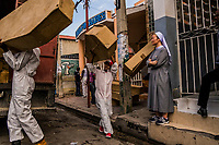 "A South Korean nun from the Kkottongnae of Jesus Foundation, looks on as workers of the St. Luc Foundation, during a collection of abandoned bodies from the premises at Zenith Funeral home - Morgue Privee premises on November 6, 2017 in Port-au-Prince, Haiti. The men step into their white medical overalls, zip them up, and then snap on latex gloves. Some fashion white palls with quilted crosses stitched on them into kerchiefs and wrap them around their heads. Others knot plastic bags around their running shoes. These are their ""blouz mò."" Their death smocks.Then, they unload the coffins, stacking them up at the mouth of a thin alley between two morgues.  The coffins are light — made from cardboard, with thin wooden frames. Soon, they will be heavy.<br /> One worker pulls out a pack of menthol cigarettes and offers them around. Another twists open a mickey of rum, tips back a bracing sip and hands it to the man beside him. It is a bonding ritual, steeling them for the grisly task ahead. <br /> They have come to collect the abandoned dead — men and women whose bodies have lost most distinctive features after weeks or months in the morgue. <br /> Photo Daniel Berehulak for The New York Times"
