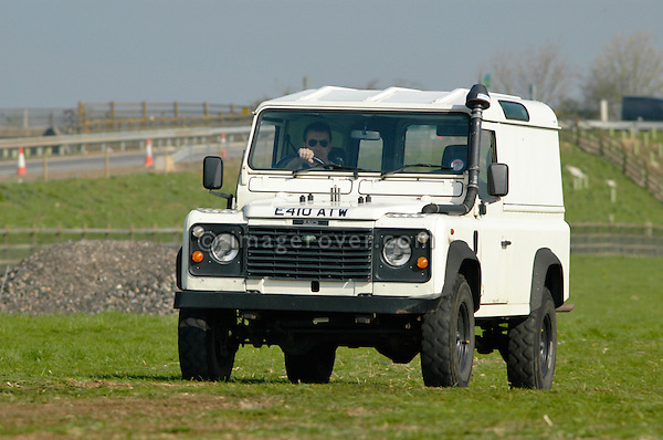 White Land Rover Defender hard top arriving at the Old Sodbury Land Rover Sortout on April 2 at Newbury Showground UK 2005. The Old Sodbury Sortout is the biggest autojumble for buying and selling Land Rover parts.