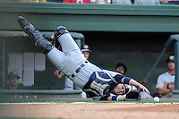 Catcher Wes Wilson (5) of the Charleston RiverDogs dives for a pop-up but misses and lands on his face in a game against the Greenville Drive on Thursday, May 16, 2013, at Fluor Field at the West End in Greenville, South Carolina. (Tom Priddy/Four Seam Images)